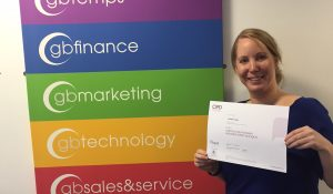 michelle large holds CIPD certiificate in front of GB Solutions logos